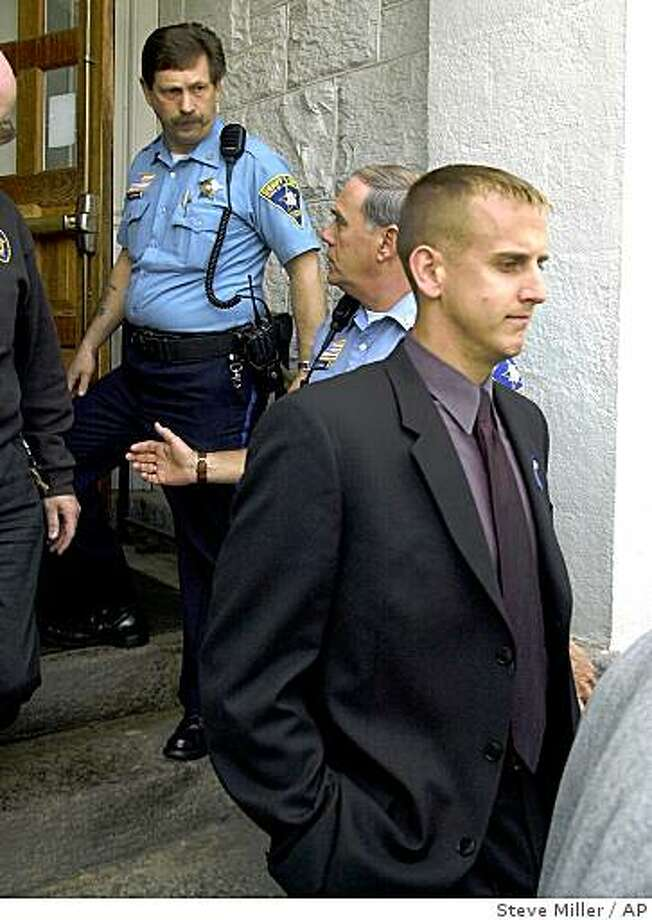 Former New Milford, Conn., police officer Scott Smith, right, leaves Litchfield Superior Court, Thursday, May 11, 2000, in Litchfield, Conn., after being sentenced to six years for the murder of Franklyn Reid during a foot chase Dec. 27, 1998. Smith is the first Connecticut police officer ever charged with murder in the line of duty and said during the trial that he thought Reid was reaching for weapon when he shot him. No weapon was found on Reid. (AP Photo/Steve Miller) Photo: Steve Miller, AP