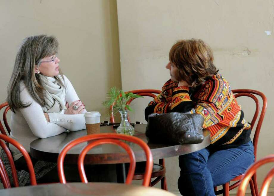 Kim Eves, left, and friend Marilyn Puder-York have coffee at Arcadia Cafe Jan. 29. Photo: Helen Neafsey / Greenwich Time