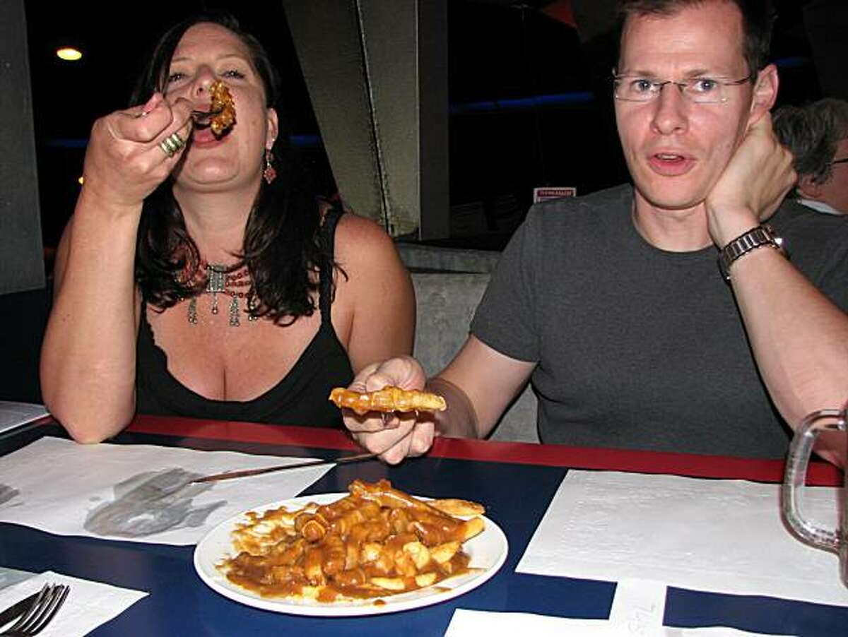 The writer's friends Kelly Konis and Ken Clemmer of Larkspur taste the french fry, cheese curd and gravy concoction known as poutine at The Flying Saucer restaurant in Niagara Falls, Ontario.
