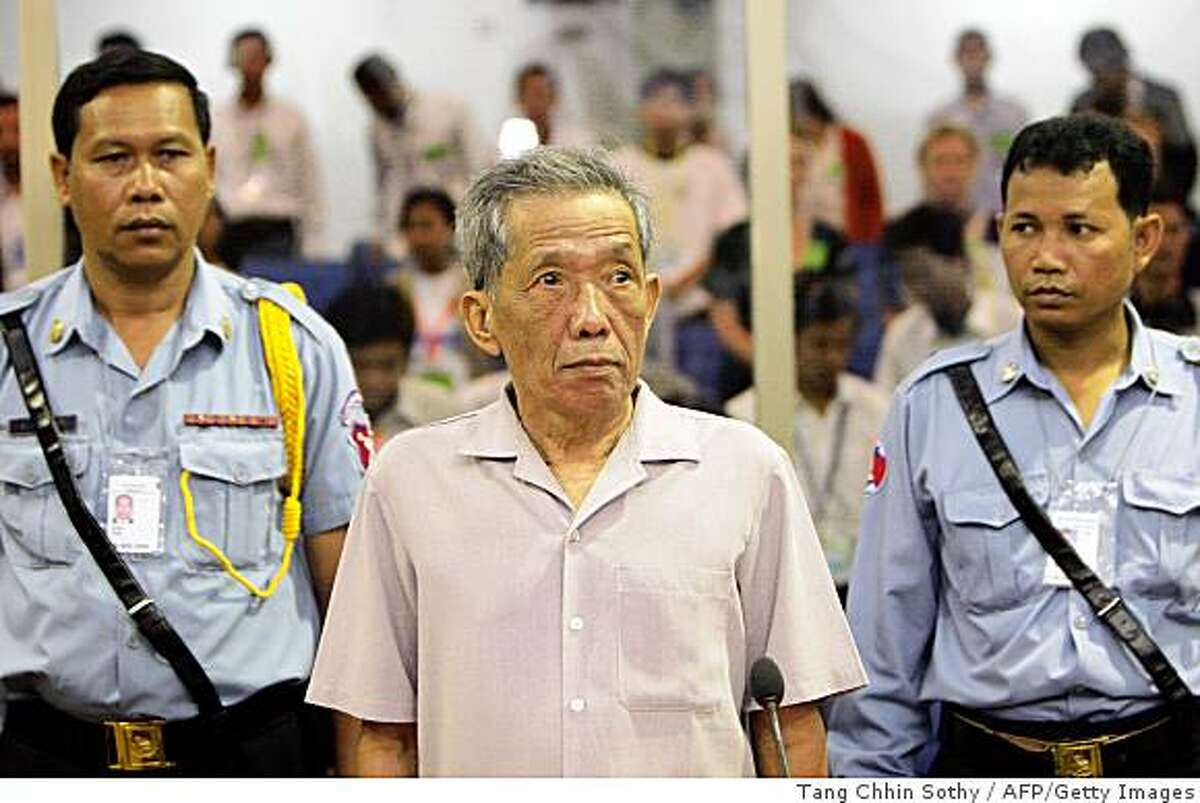 """Former Khmer Rouge prison chief S-21, Kaing Guek Eav better known as """"Duch"""" (C) stands in the court room at the Extraodinary Chambers in the Courts of Cambodia in Phnom Penh on December 5, 2008. Cambodia's former Khmer Rouge prison chief appeared on December 5, before the country's genocide court as it decides whether a charge that could have wide-ranging effects on other regime leaders should be added to his indictment. AFP PHOTO/POOL/TANG CHHIN SOTHY (Photo credit should read TANG CHHIN SOTHY/AFP/Getty Images)"""