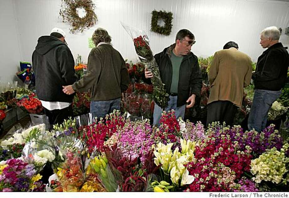 Tim Jordan (middle) is surrounded by mostly men as they shop for  flowers a day before Valentines Day at Greenworks in the Flower Mart in San Francisco, California, on February 13, 2009. Photo: Frederic Larson, The Chronicle