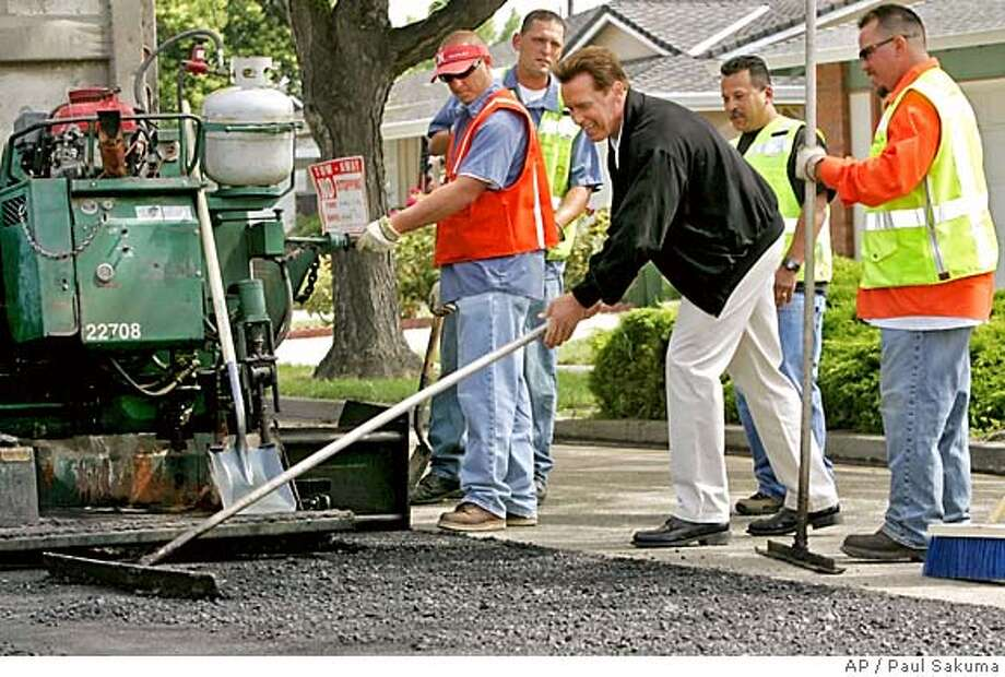 Calif. Gov. Arnold Schwarzenegger uses a tool to help grade a road in San Jose, Calif., as road workers watch, Thursday, May 26, 2005. Schwarzenegger discussed full funding of Proposition 42 transportation funds in his revised budget. (AP Photo/Paul Sakuma) Gov. Arnold Schwarzenegger smiles as he helps smooth out the surface of a hole San Jose city crews dug for his media event. Photo: PAUL SAKUMA
