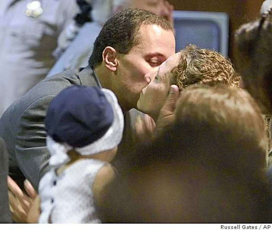 Former Chandler police Officer Dan Lovelace turns around and kisses his wife, Trish Lovelace, after he was acquitted Friday, July 9, 2004, in Mesa, Ariz., of second-degree murder and endangerment charges in shooting death of an Ahwatukee woman. (AP Photo/Pool, Russell Gates) Photo: Russell Gates, AP