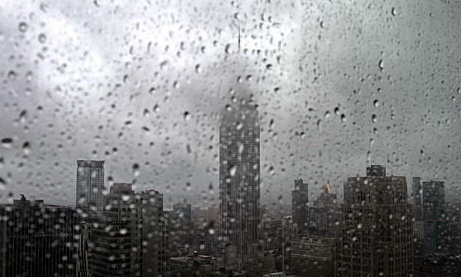 As rain covers a window with droplets, fog partially hides the Empire State building, center, in New York, Tuesday, Sept. 28, 2010.  The National Weather Service has issued a tornado watch for all of New York City, Nassau County and northern counties extending through Oneida County. Photo: Bebeto Matthews, AP