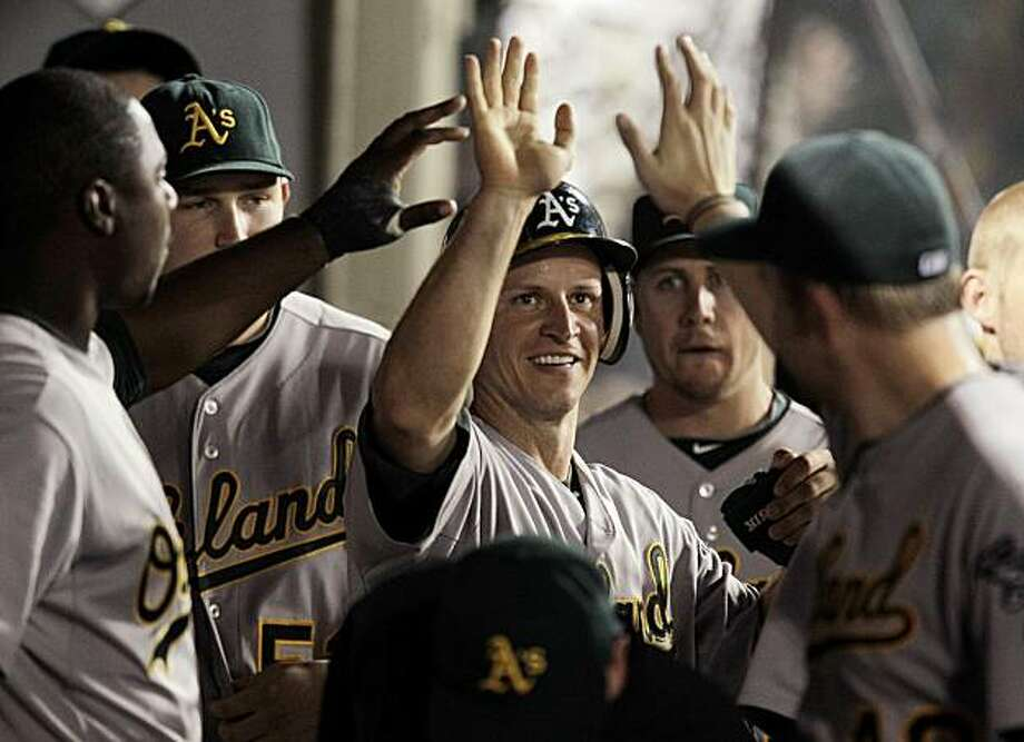 Oakland Athletics' Mark Ellis, center, is greeted by his teammates after Ellis scored on Jack Cust's single in the fourth inning of a baseball game with the Los Angeles Angels in Anaheim, Calif., Monday, Sept. 27, 2010. Photo: Jae C. Hong, AP