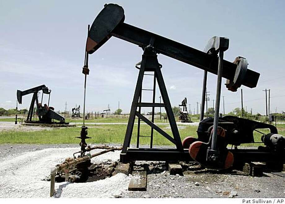 Oil pump jacks work in a field near the Houston Ship Channel Monday, July 14, 2008  in Baytown, Texas. Oil prices settled above $145 a barrel after swinging between gains and losses as traders weighed global supply concerns and a mixed dollar against worries about the health of the U.S. economy. (AP Photo/Pat Sullivan) Photo: Pat Sullivan, AP