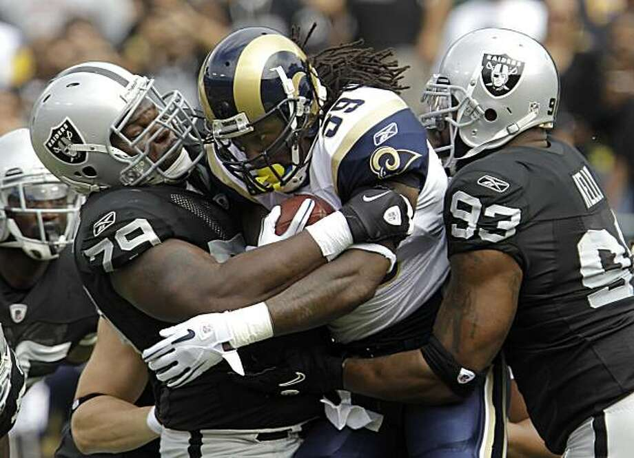 St. Louis Rams running back Steven Jackson (39) is tackled by Oakland Raiders defensive tackle John Henderson (79) and defensive tackle Tommy Kelly (93) in the first quarter of an NFL football game in Oakland, Calif., Sunday, Sept. 19, 2010. Photo: Paul Sakuma, AP