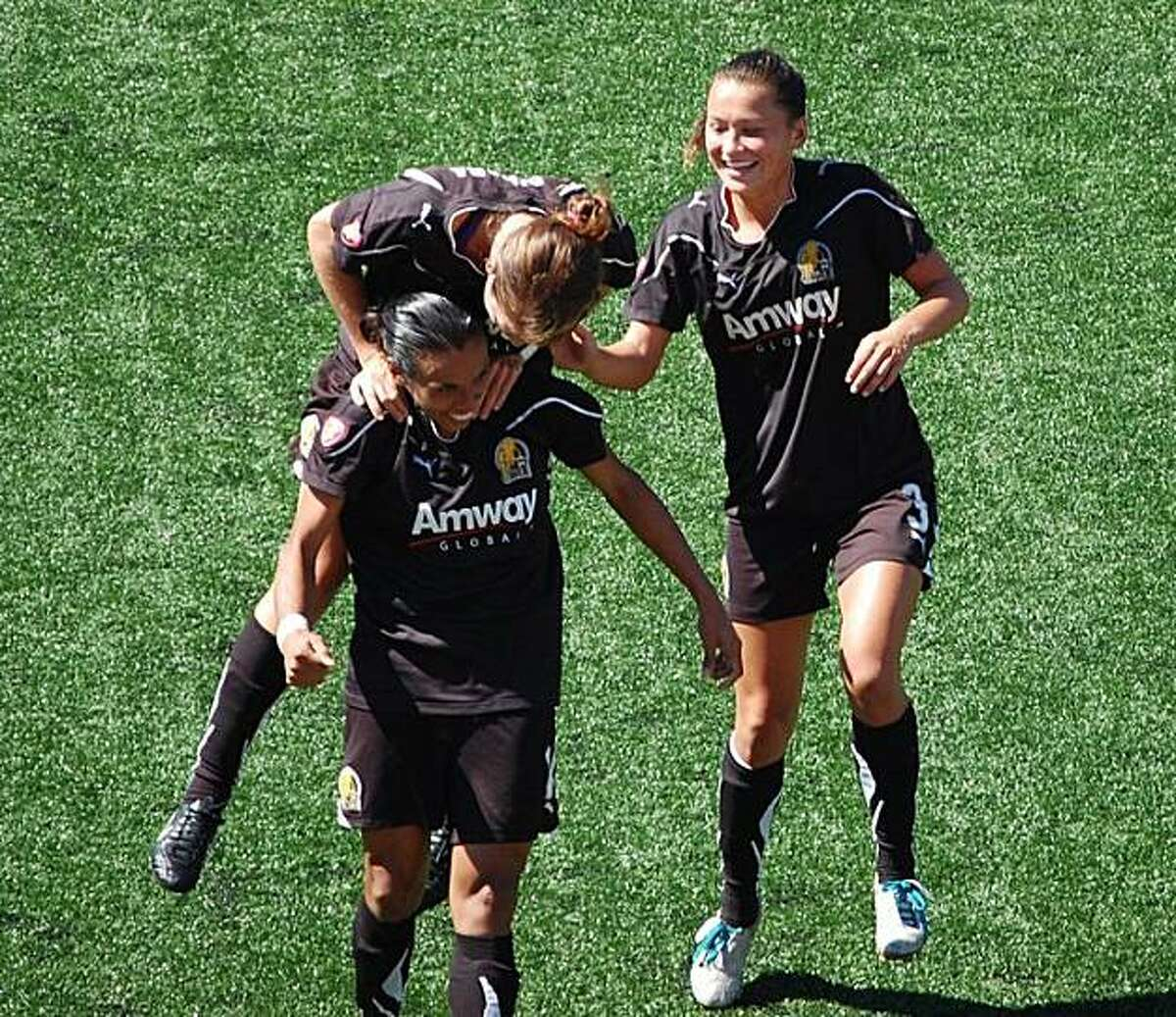 The FC Gold Pride's Marta, bottom left, celebrates her goal in second half extra time with her teammates Kelley O'Hara, top left, and Ali Riley, right, during the WPS Championship game. The Pride once again rode the skills of Brazilian great Marta to a 4-0 rout of the Philadelphia Independence before a crowd of 5,228 at Cal State East Bay in Hayward, Calif on Sunday, September 26, 2010.