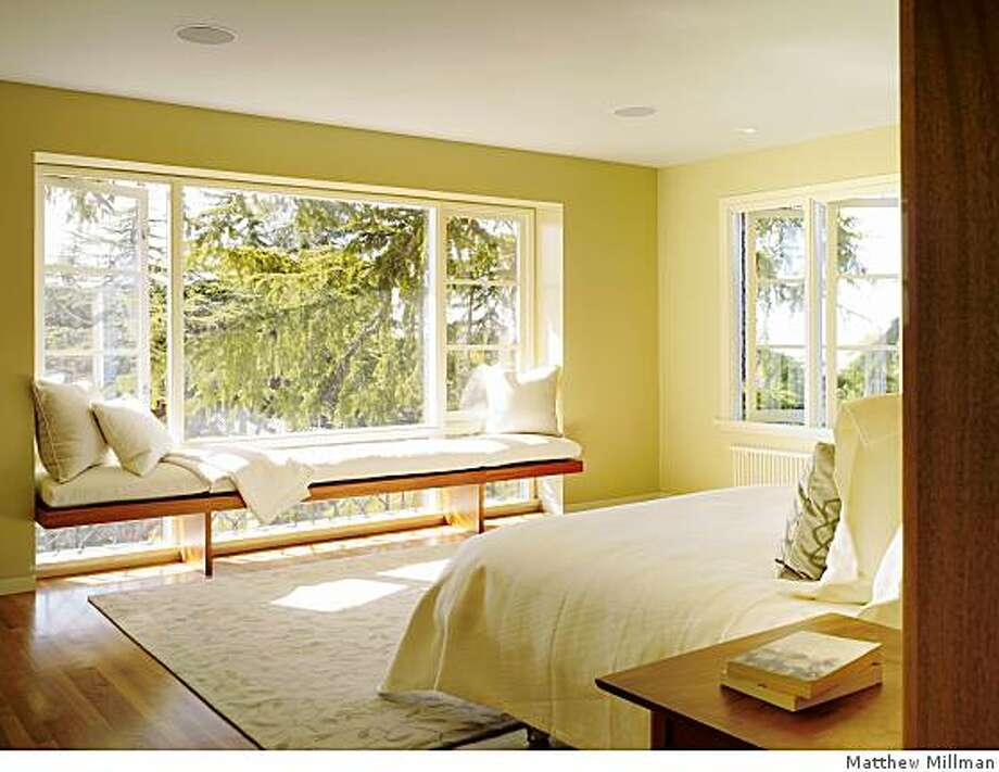 Neal Schwartz and his team of four designers gutted the rooms of this Oakland home to form a single big space in which a new floor-to-ceiling 11 by 8.6-foot rectangular mahogany box acts as a room divider.Light streams into the bedroom around each side of a mahogany box that also doubles as a dramatic backdrop for the bed and conceals a walk-in closet and powder room. Photo: Matthew Millman