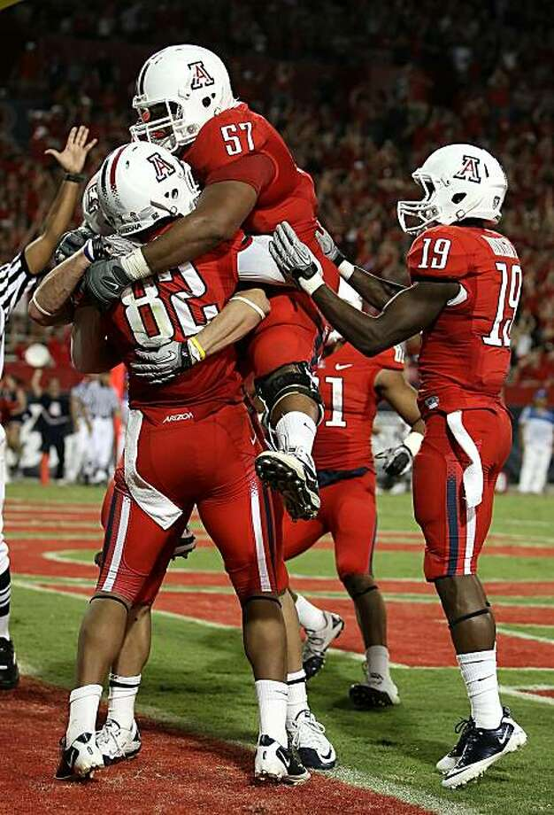 TUCSON, AZ - SEPTEMBER 25:  Jovon Hayes #57 of the Arizona Wildcats jumps into the arms of wide receiver Juron Criner #82 after Criner caught the game winning 3 yard touchdown reception against the California Bears during the fourth quarter of the collegefootball game at Arizona Stadium on September 25, 2010 in Tucson, Arizona. The Wildcats defeated the Bears 10-9. Photo: Christian Petersen, Getty Images