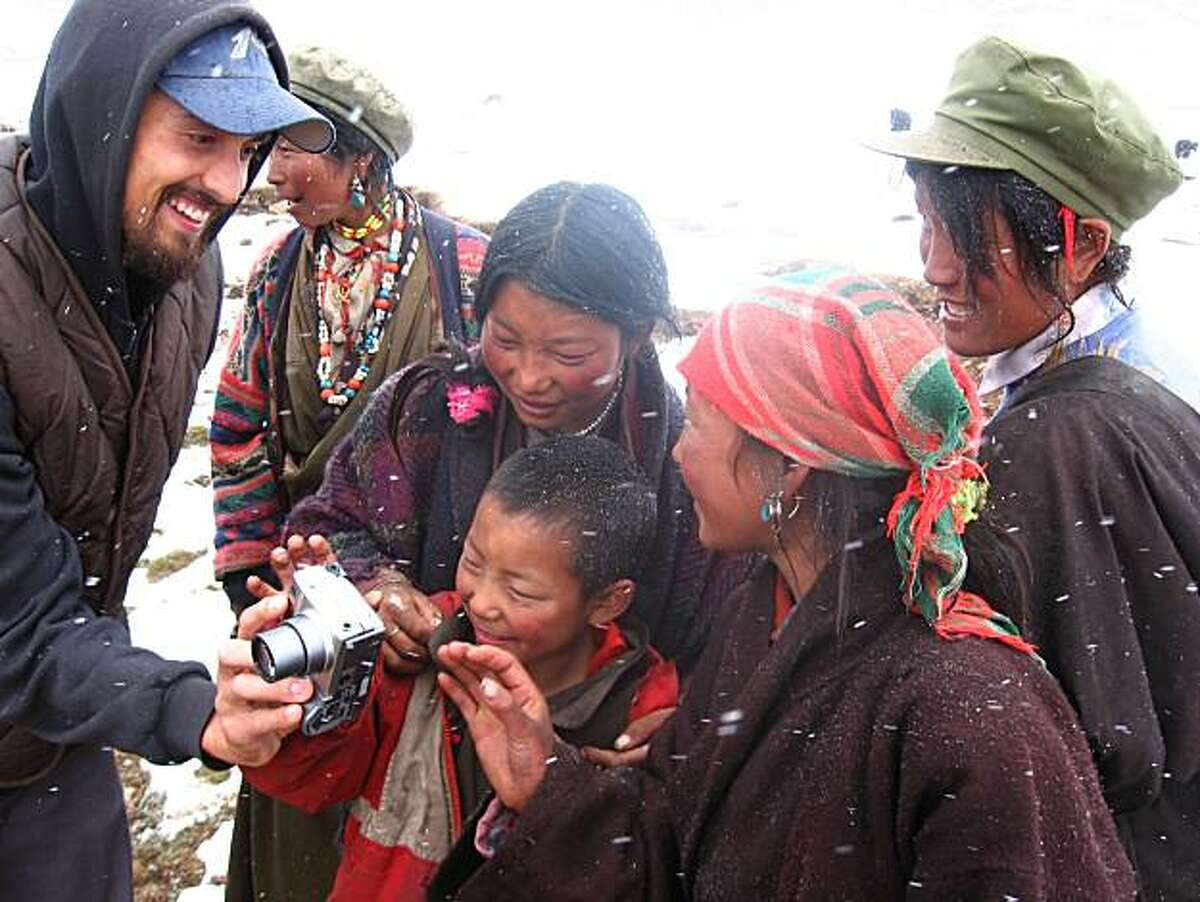 Tom Carter, left, shows camera to locals in Tibet. The San Francisco native spent four years roaming the country,