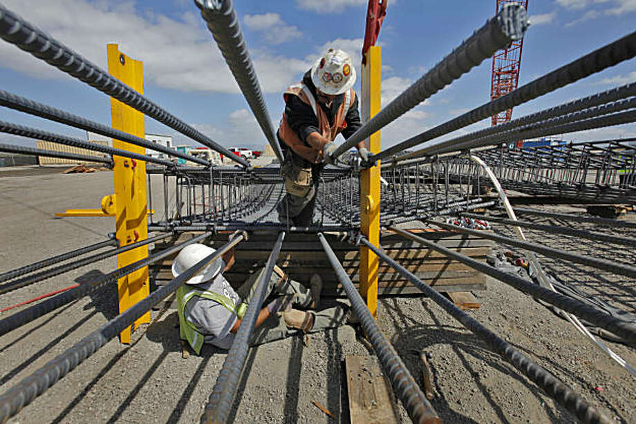 Melchar Solorio, below and Jorge Martinez, of the Bencor Corporation, work on connecting the rebar panels to support beams as a part of the new tunnel project, which is a $4.6 billion water system upgrade, Tuesday Sept. 21, 2010, in Menlo Park, Calif. Photo: Lacy Atkins, The Chronicle