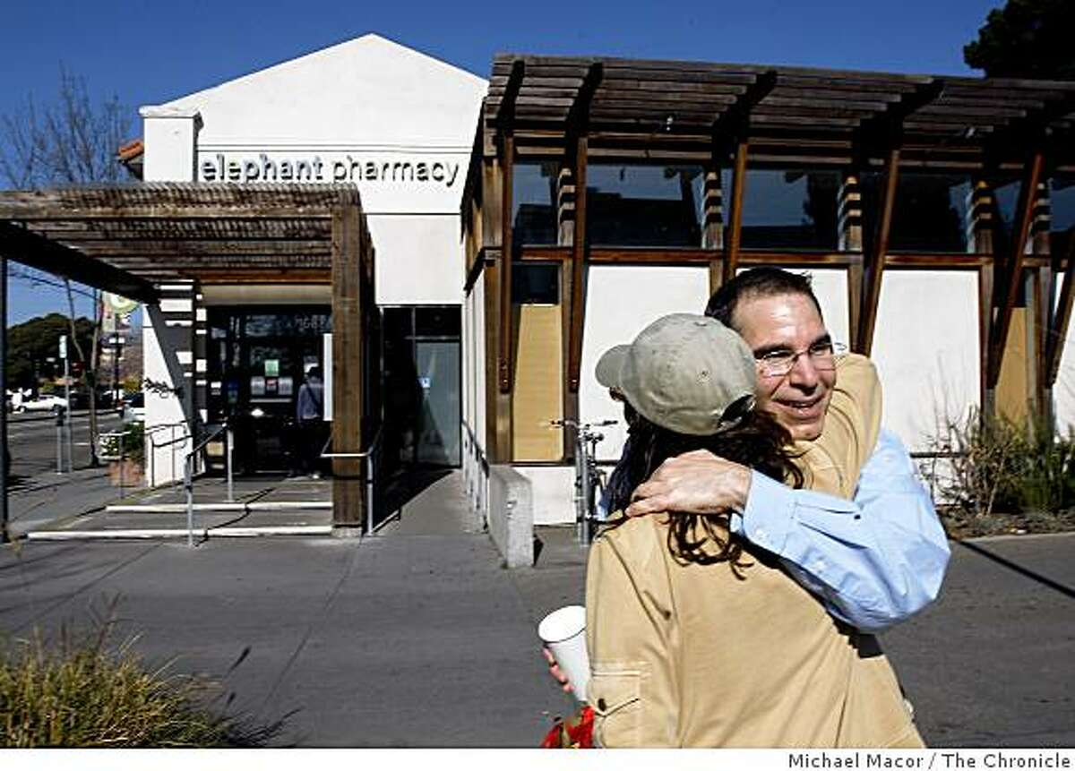 Long-time customer, Keith Gatto hugs employee Brenda Dunn, who worked at the store for almost five yrears, as Elephant Pharm, the Berkeley-based drug store chain known for it's holistic approach to health care abruptly shut it's doors and filed for bankruptcy protection on Tuesday Feb. 3, 2009.