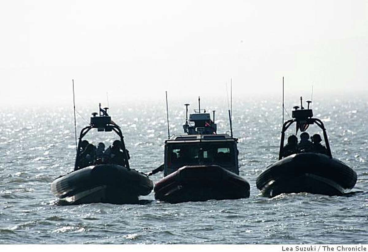 U.S. Coast Guard boats participating in a training exercise wait in a group in the San Pablo Bay before starting the training exercise using an armed helicopter on Monday, February 2, 2009.