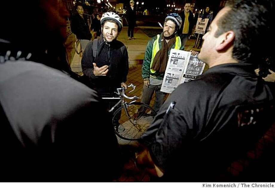 Two protesters identifying themselves as Josh (left) and Max (right) talk with Oakland Police officers as a crowd begins to gather in front of Oakland City Hall on Jan. 31, 2009, a day after former BART officer Johannes  Mehserle was granted bail in the shooting death of Oscar Grant. Photo: Kim Komenich, The Chronicle