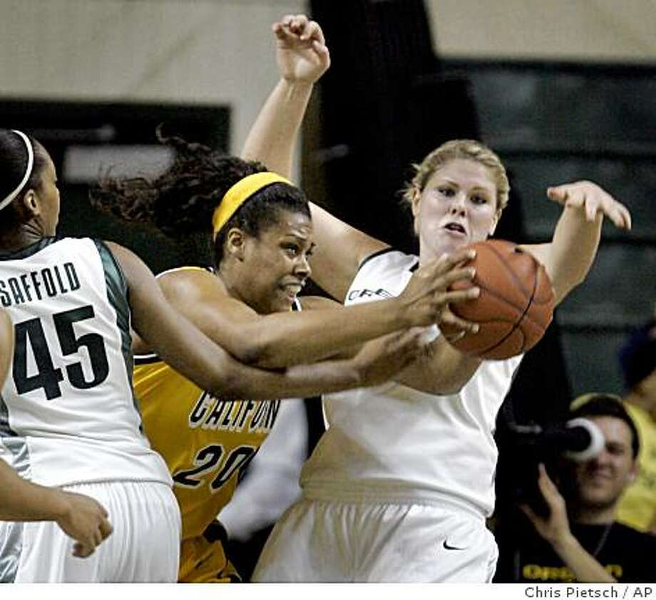 California's Devanei Hampton, center, comes up with a rebound against Oregon's Lindsey Saffold, left, and Ellie Manou, right, during the first half of an NCAA college basketball game in Eugene, Ore. Saturday Jan. 24, 2009.  (AP Photo/Chris Pietsch) Photo: Chris Pietsch, AP