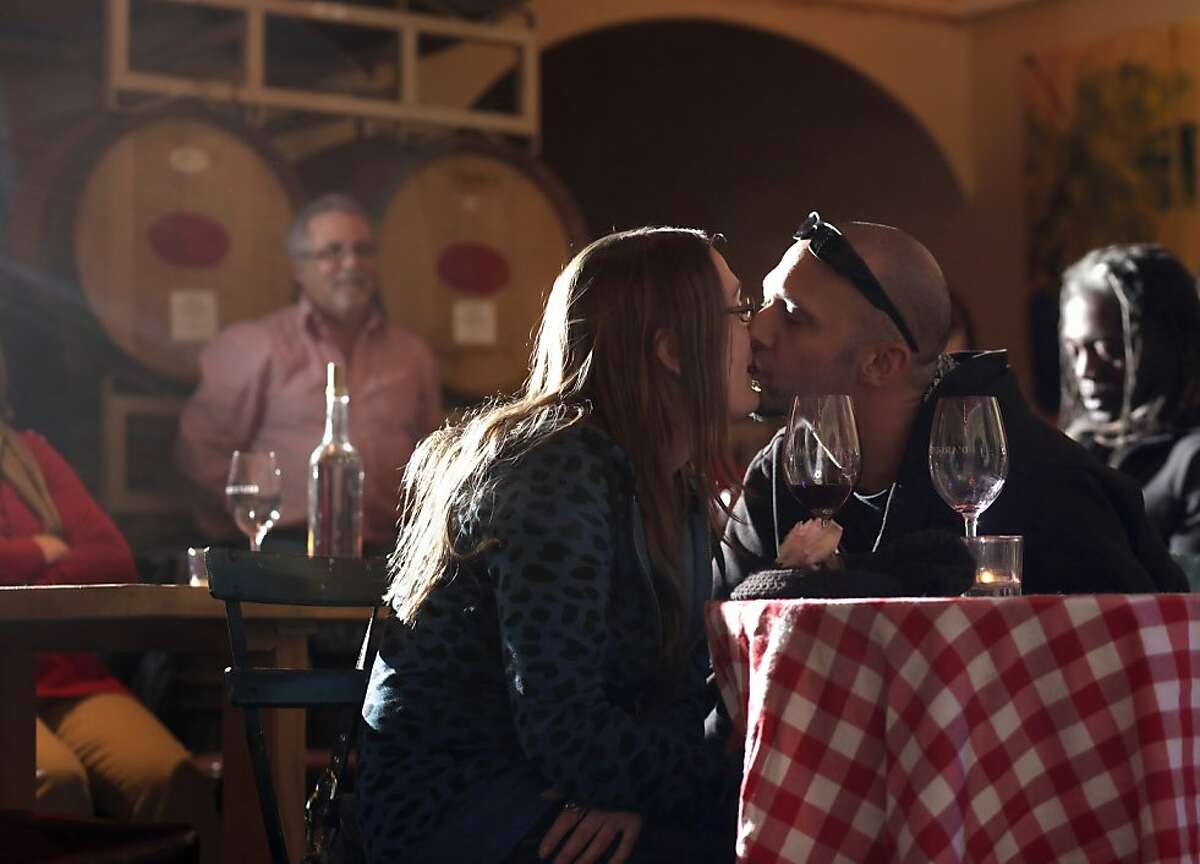 Amber Richards and Michael Whitt kiss as they listen to music and enjoy a little wine at the D'Argenzio Winery, Thursday January 5, 2012, in Santa Rosa Calif.