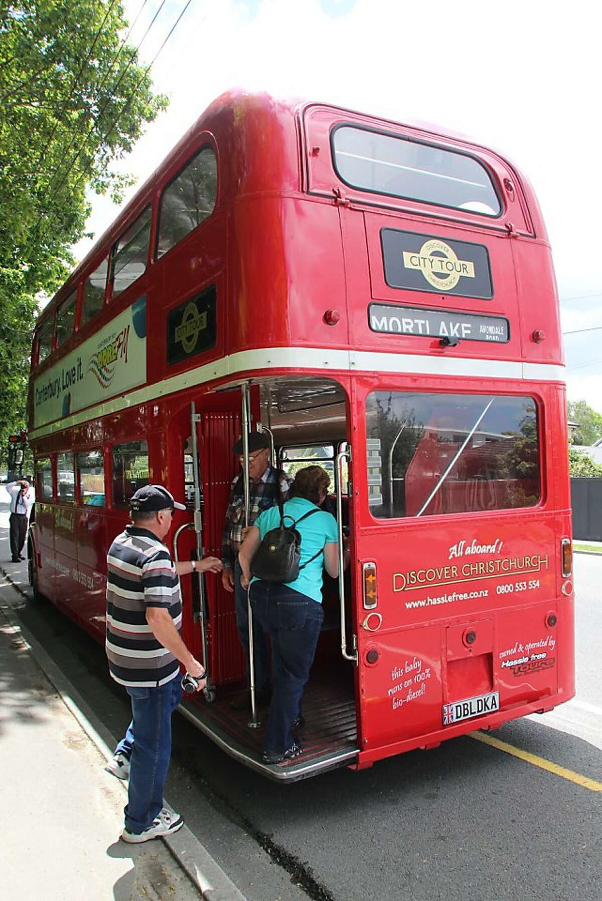 Passengers board an original London double-decker bus for a city tour of Christchurch, N.Z., that focuses on the destruction from that city's earthquakes, as well as on attractions that escaped damage.