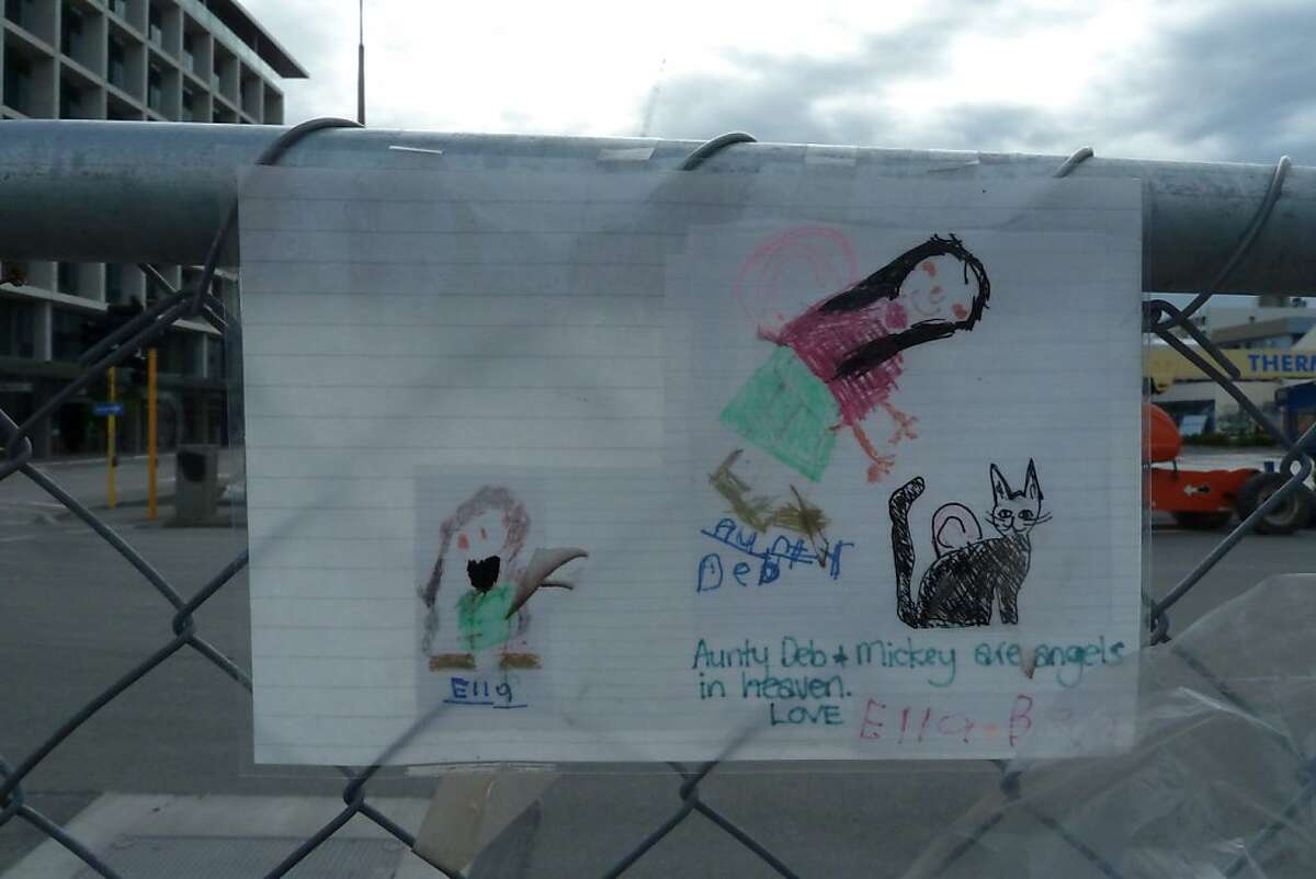 """Memorials left at the fence circling downtown include a child's note that """"Aunty Deb & Mickey are angels in heaven."""""""