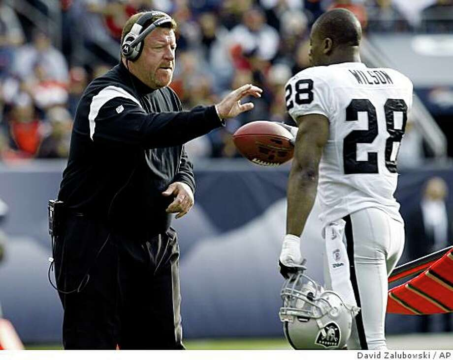 Oakland Raiders head coach Tom Cable, left, reaches out to congratulate safety Gibril Wilson as he returns to the sidelines after picking up a fumble to stifle a drive by the Denver Broncos in the first quarter of an NFL football game in Denver on Sunday, Nov. 23, 2008. (AP Photo/David Zalubowski) Photo: David Zalubowski, AP