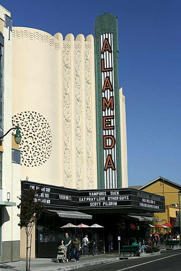 Families walk past the Alameda Theatre, August. 8, 2010, in Alameda, Calif.  Alameda, a nineteenth-century bedroom community for San Francisco that is now struggling to plan for future growth, has preserved its small-town feel. Photo: Adm Golub, The Chronicle