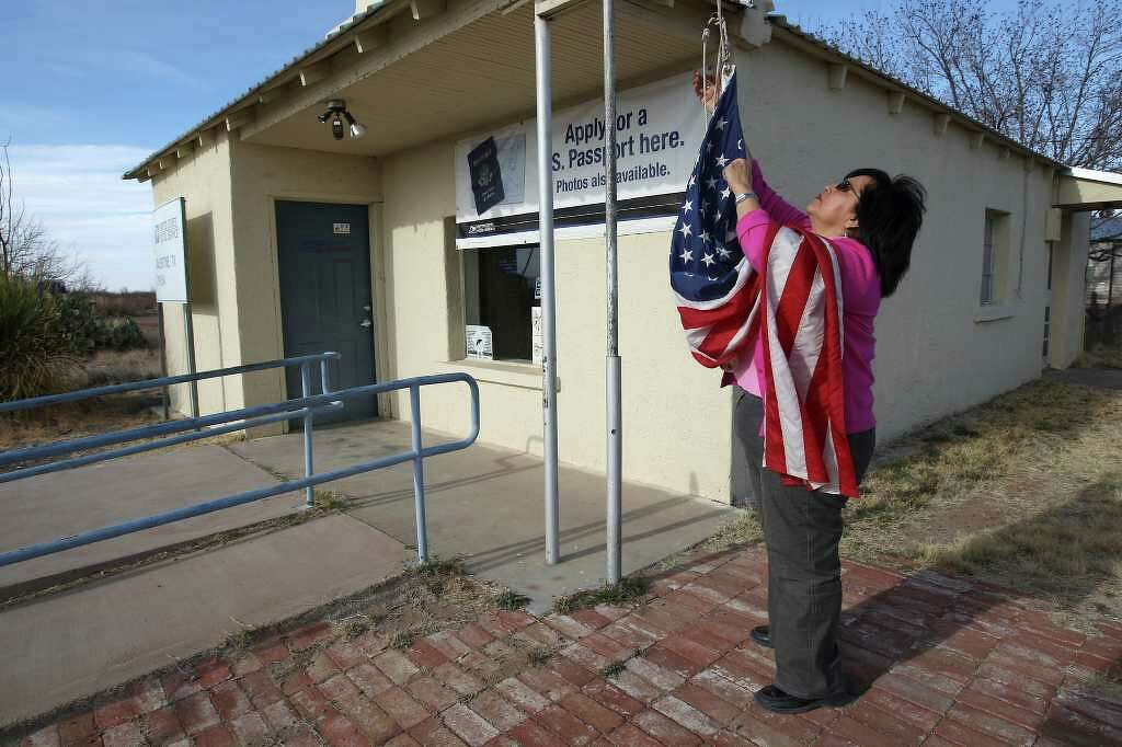 At The End Of The Day, U.S. Postmaster Maria Carrasco Lowers The U.S. Flag  Outside