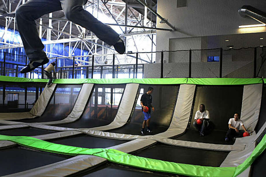 House of Air Flight visitor's feet dangle in the air while trying to slam dunk a basketball in the The Colosseum, 22 conjoined trampolines, at House of Air in San Francisco, Calif. on Wednesday September 15, 2010. Photo: Lea Suzuki, The Chronicle