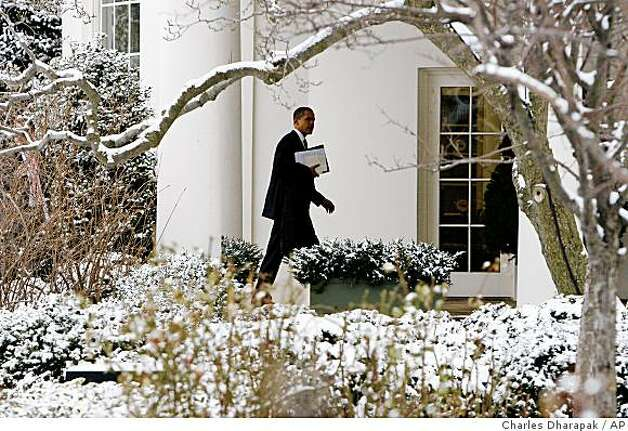 Snow is seen on the south grounds of the White House in Washington, Tuesday, Jan. 27, 2009, as President Barack Obama walks back to the Oval Office after a trip to Capitol Hill to meet House and Senate Republicans. (AP Photo/Charles Dharapak) Photo: Charles Dharapak, AP