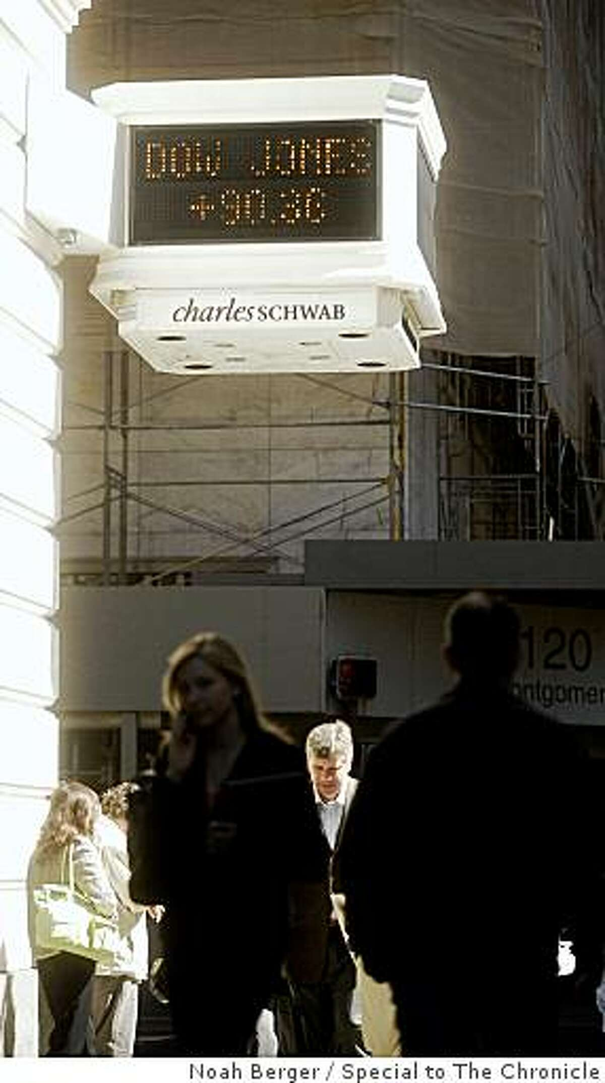 Pedestrians pass a ticker display outside Charles Schwab?s San Francisco offices on Monday, March 17, 2008. BY NOAH BERGER/SPECIAL TO THE CHRONICLE