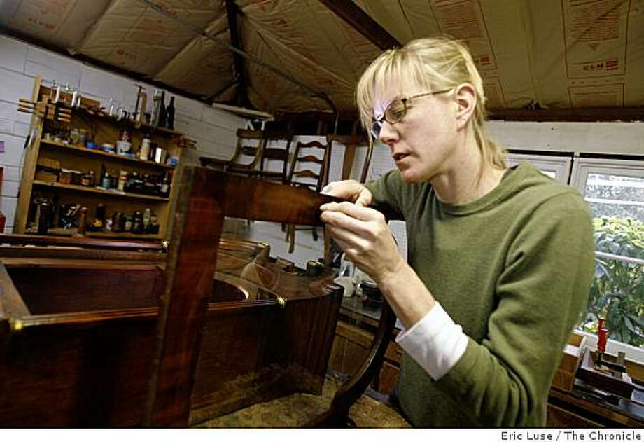Sarah Johnson of Fairfax restores furniture, including some rare 18th Century pieces. Here she works on an English country clock. Photo: Eric Luse, The Chronicle