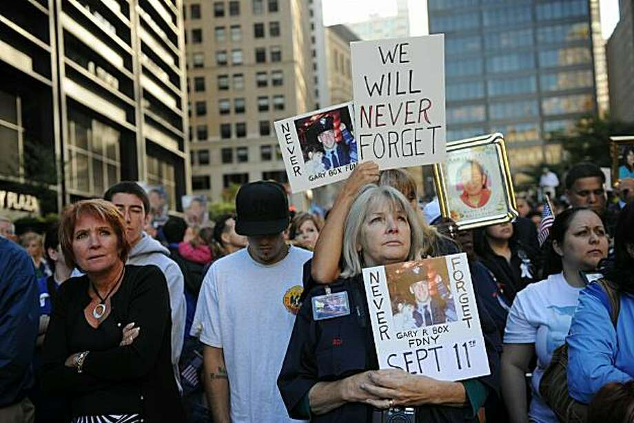 Mourners holding pictures of pf family memebers gather around a reflecting pool in memory of victims of the 9/11 terrorist attacks September 11, 2010 in New York City. Thousands gathered to pay a solemn homage on the ninth anniversary of the terrorist attacks that killed nearly 3,000 people on September 11, 2001. Photo: Pool, Getty Images