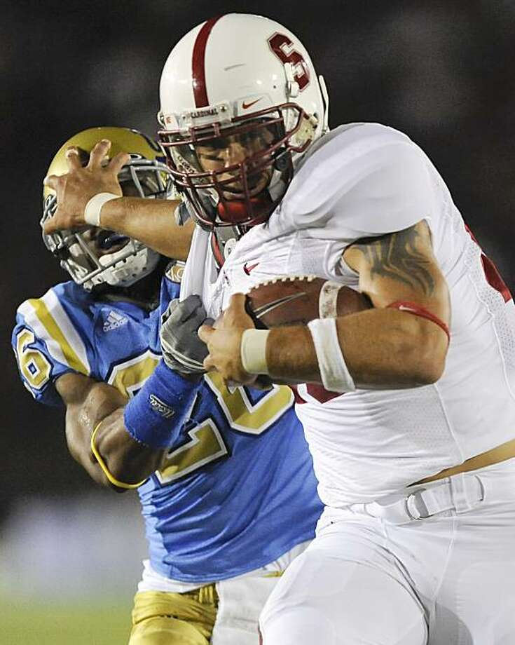 Stanford running back Tyler Gaffney, right, stiff-arms UCLA cornerback Andrew Abbott (26) as he runs for a first down during the first half of an NCAA college football game, Saturday, Sept. 11, 2010, in Pasadena, Calif. Photo: Gus Ruelas, AP