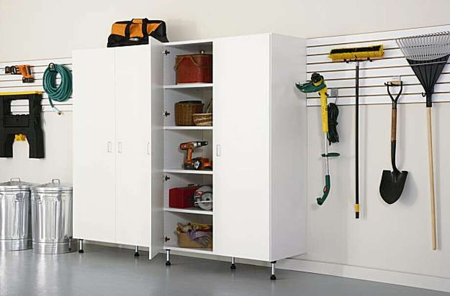 A garage gives you three solid walls you can use for storage.  Steel, wood-grain and melamine-laminated particle board cabinet systems can give you closed storage for items you want away from the elements. Photo: Courtesy ClosetMaid