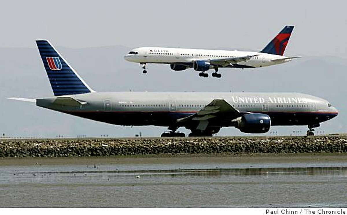 A Delta Airlines jet prepares to land while a United Airlines plane awaits clearance for takeoff at San Francisco International Airport on Wednesday, March 26, 2008. The two airlines on Tuesday reported a combined first-quarter loss of nearly $1.2 billion. Photo by Paul Chinn / San Francisco Chronicle