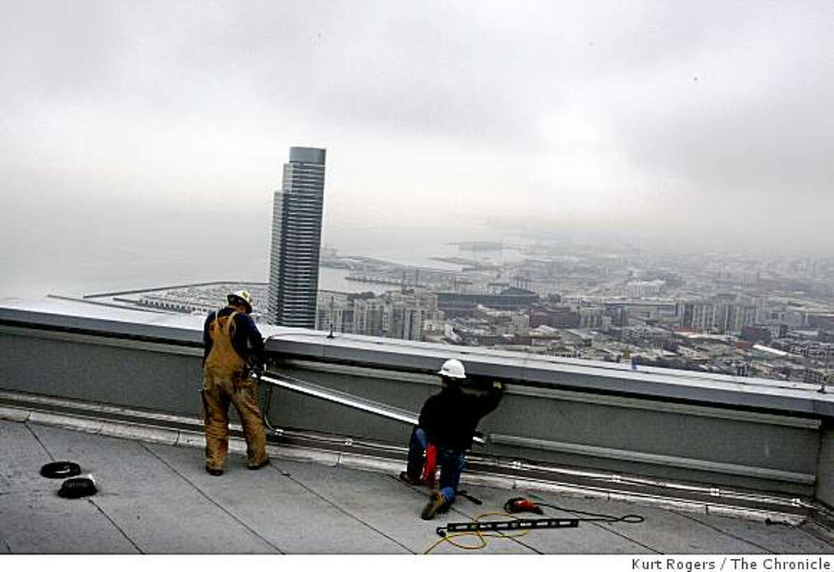 Dennis Morrison (left) of Hayward and Bobby Stack of San Francisco put some finishing touches on the top of the Millennium Building on Thursday Jan. 22, 2009 in San Francisco, Calif.