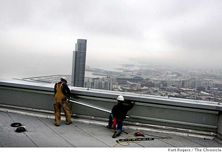 Dennis Morrison (left) of Hayward and Bobby Stack of San Francisco put some finishing touches on the top of the Millennium Building on Thursday Jan. 22, 2009 in San Francisco, Calif. Photo: Kurt Rogers, The Chronicle