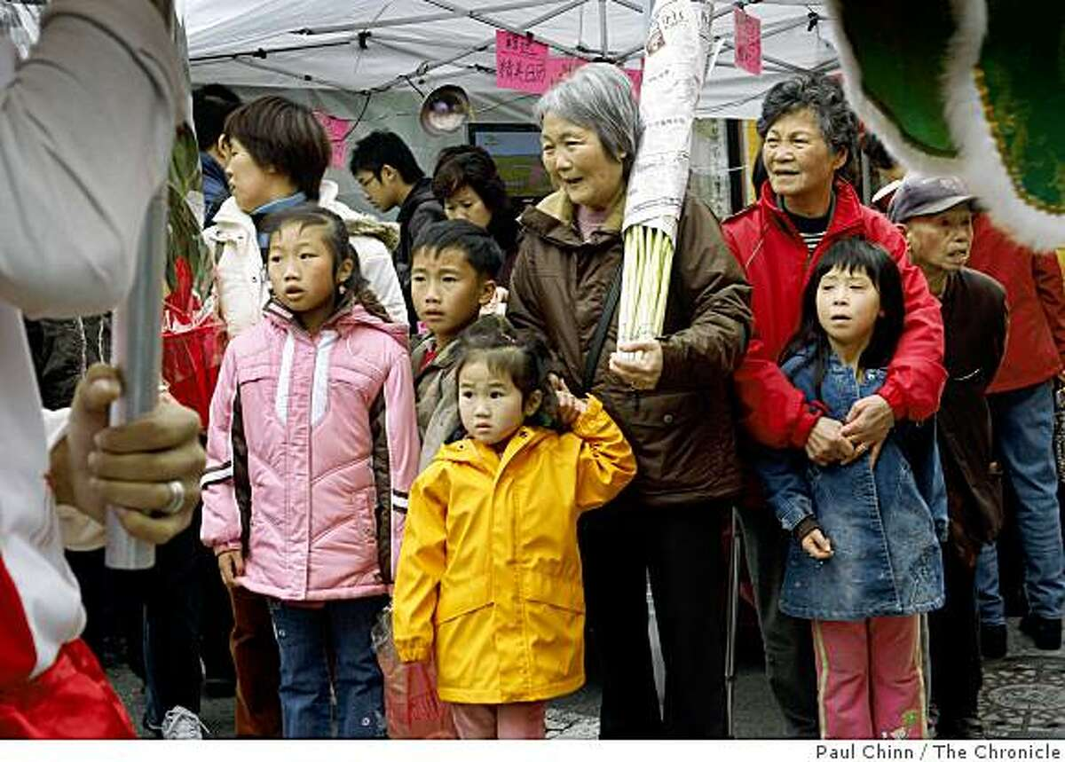 People of all ages attending a Chinatown street fair watch Gum Lung the golden dragon parade on Grant Avenue in San Francisco, Calif., on Saturday, Jan. 24, 2009.