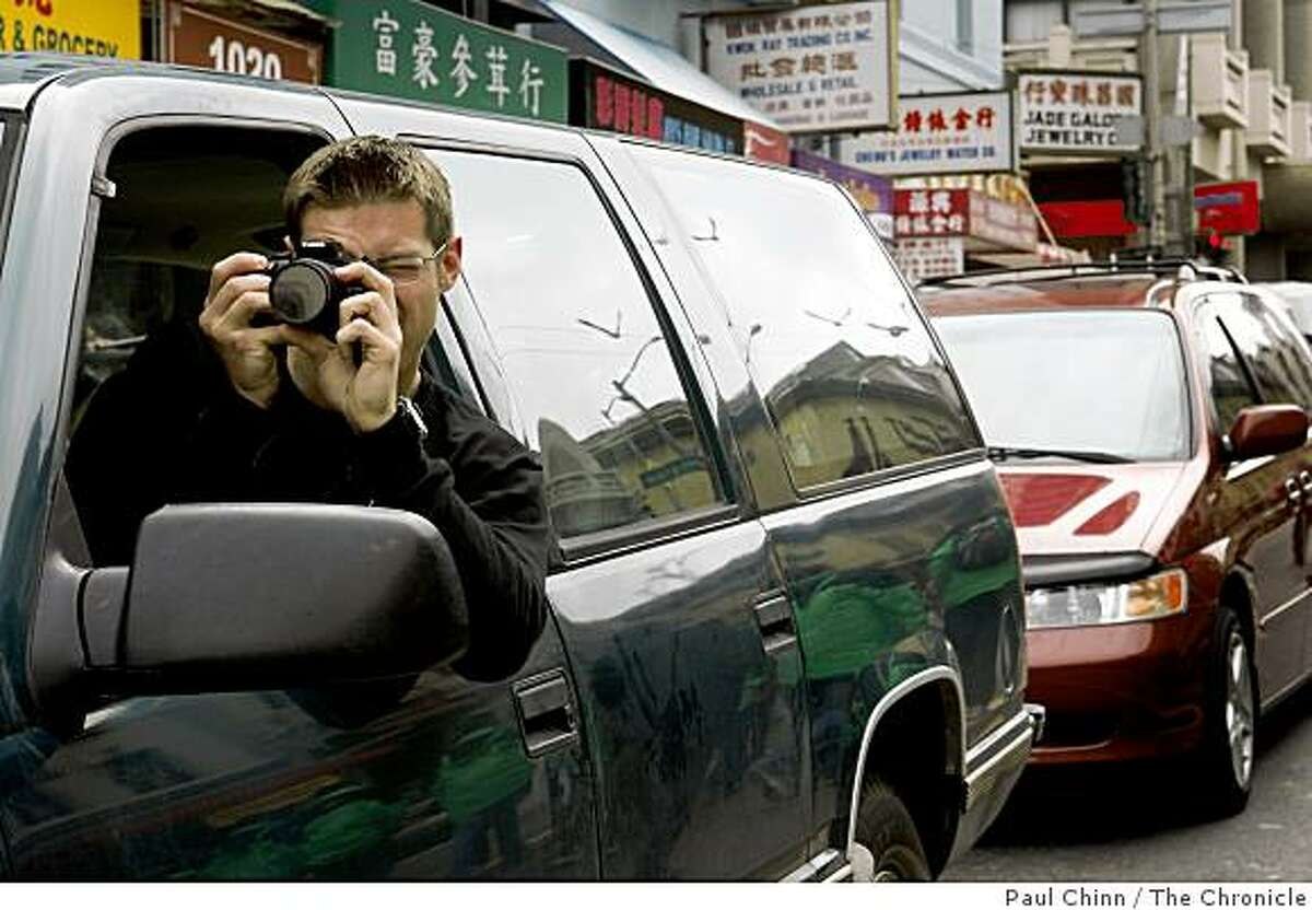 Bill Jay, who got stuck in traffic during a pre-Chinese New Year mini-parade on Stockton Street, leans out of his window to snap a photo of Gum Lung the golden dragon in San Francisco, Calif., on Saturday, Jan. 24, 2009.