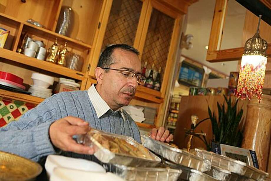 "From left, Osman Othman, the owner of  Oasis Market arrnges the sweets in the bakery of the busymarket/restaurant/bakery on Telegraph Ave in Oakland, Calif. on Wednesday, September 8, 2010.  Othman said he objects to the proposed parolee center moving in down the street because ""I don't even sell liquor or cigarettes in my store because we want families in here and we are trying to build up the reputation of this neighborhood."" A nonprofit working with the state department of corrections and rehabilitation wants to open a day center for parolees in the Koreatown Northgate district of Oakland, which is on Telegraph Avenue from 20th to 35th streets. But this center is at odds with how the district sees itself: as an emblem of a revitalization.  Kat Wade / Special to the Chronicle Photo: Kat Wade, Special To The Chronicle"