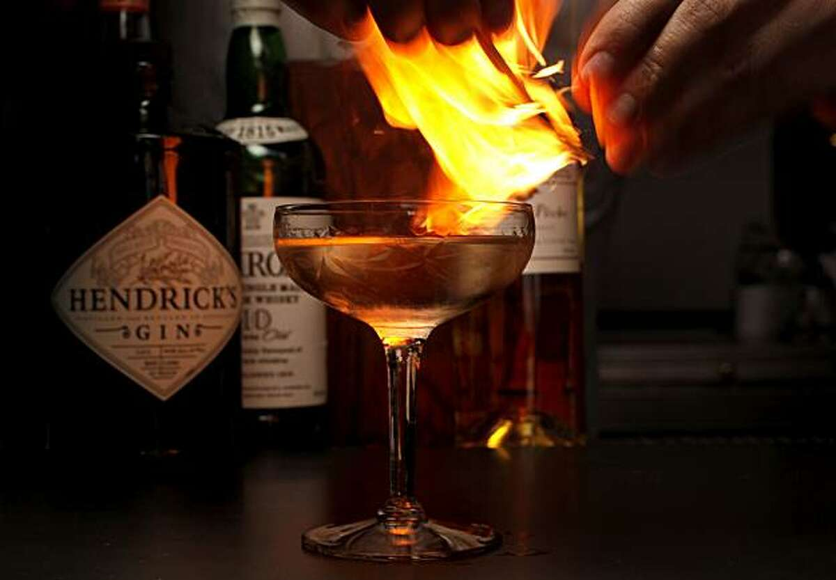 Bar manager Morgan Schick adds a flaming orange rind to finish his specialty drink, a