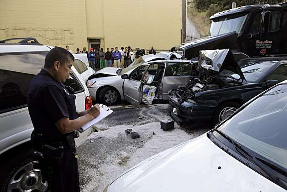 Oakland Police investigate an accident on the Grand Avenue off ramp of east-bound Highway 580 on Wednesday evening, September 8, 2010. A trailer carrying a dumpster reportedly lost its brakes hitting several vehicles causing a chain reaction accident. Four people were transported to local hospitals, but police had no details on their conditions. Photo: Carlos Avila Gonzalez, The Chronicle