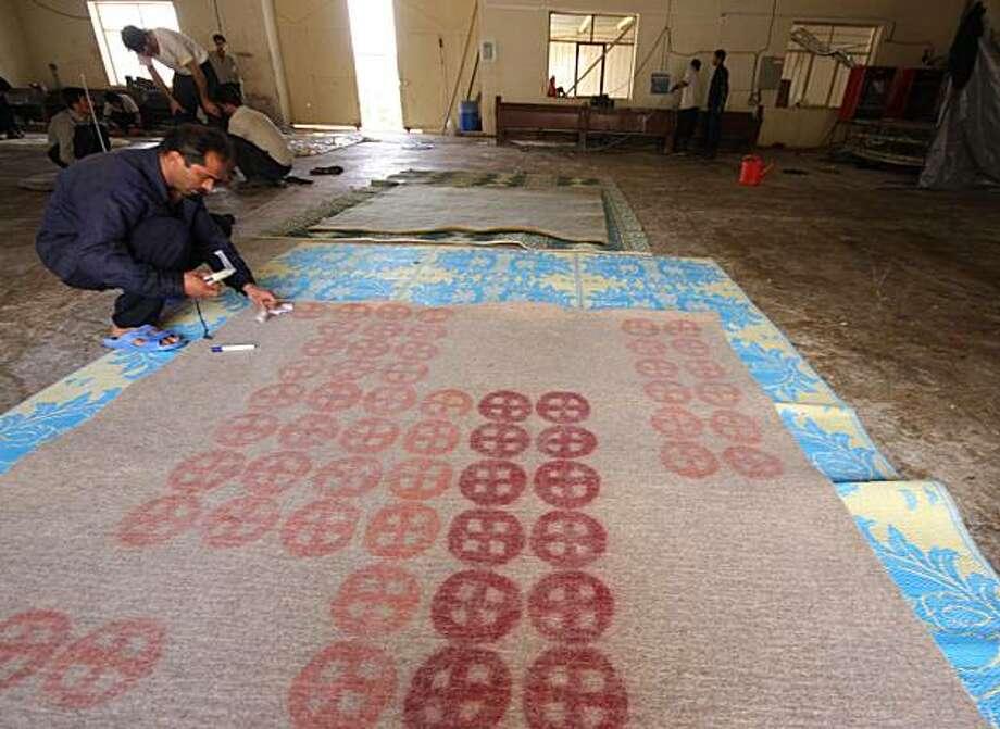 Iranian workers create felt rugs for export in Iran. Photo: Melina Raissnia, Melina Raissnia/Peace Industry