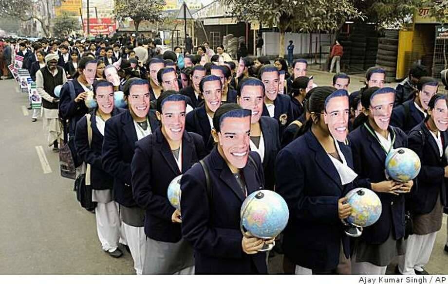 School children wear masks of U.S. President-elect Barack Obama as they take out a procession to mark his inauguration in Lucknow, India, Tuesday, Jan. 20, 2009. Barack Obama steps into history by becoming the United States' first black president Tuesday, bringing a message of hope to a nation battered by recession, weary of war and hungry for change after eight years of George W. Bush in the White House. (AP Photo/Ajay Kumar Singh) Photo: Ajay Kumar Singh, AP