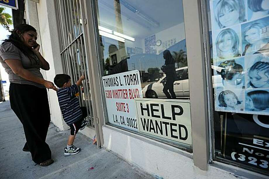 "A woman and her stand wait outside a beauty salon with a ""Help Wanted"" sign in the window, in East Los Angeles, California on September 3, 2010. A better-than-expected report on employment September 3 was the latest piece of improving news on the economy.The Labor Department said companies added 67,000 jobs in August, more than analysts expected. Photo: Robyn Beck, AFP/Getty Images"
