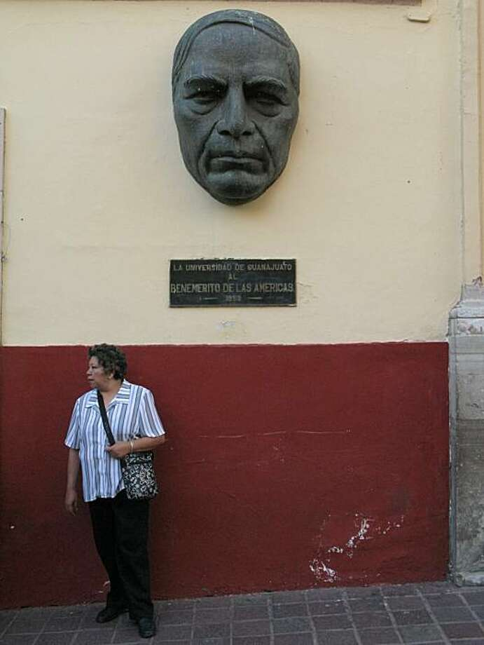 A woman stops for moment under the watchful eyes of a sculpture in central Guanajuato. Photo: Spud Hilton, The Chronicle