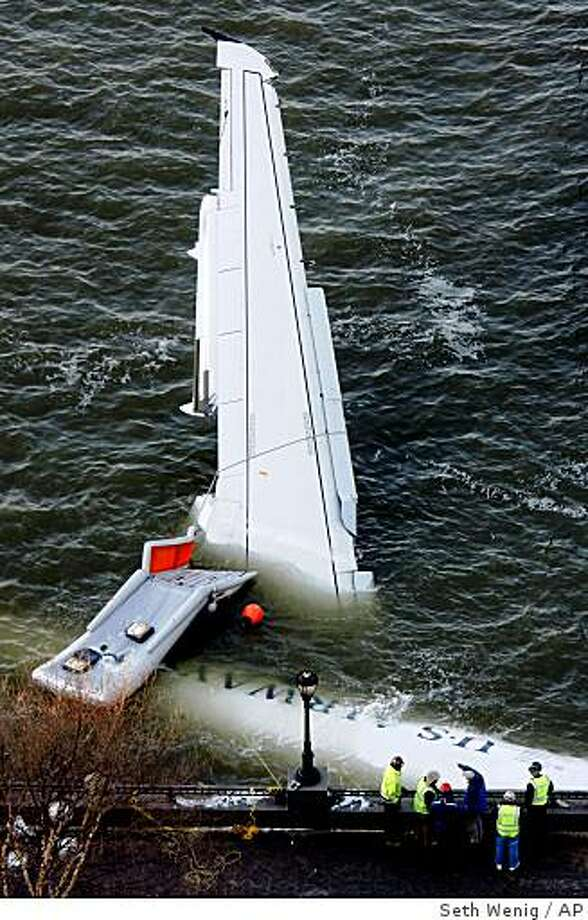 Emergency personnel look over a submerged U.S. Airways plane that crashed into the Hudson River on Thursday and was towed to the Manhattan shoreline for further inspection in New York, Friday, Jan. 16, 2009.  (AP Photo/Seth Wenig) Photo: Seth Wenig, AP