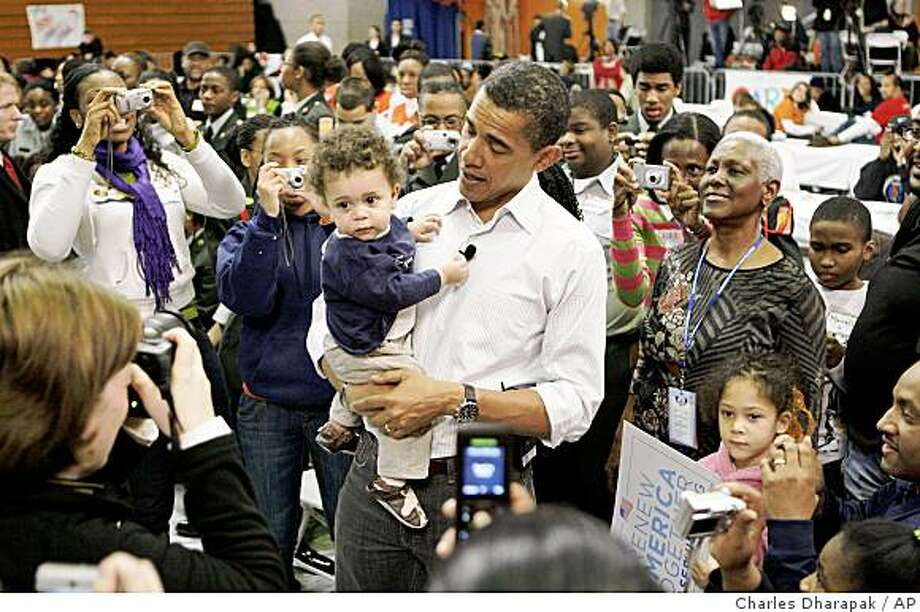 President-elect Barack Obama holds Charles Rollins, 1, of Chevy Chase, Md., as he visits a community service project for troops at Calvin Coolidge High School in Washington, Monday, Jan. 19, 2009. Photo: Charles Dharapak, AP