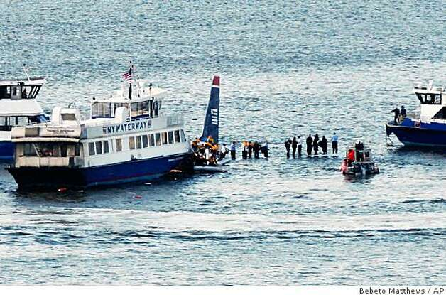 Ferry boats surround a US Airways aircraft that has gone down in the Hudson River in New York, Thursday Jan. 15, 2009. It was not immediately clear if there were injuries. (AP Photo/Bebeto Matthews) Photo: Bebeto Matthews, AP