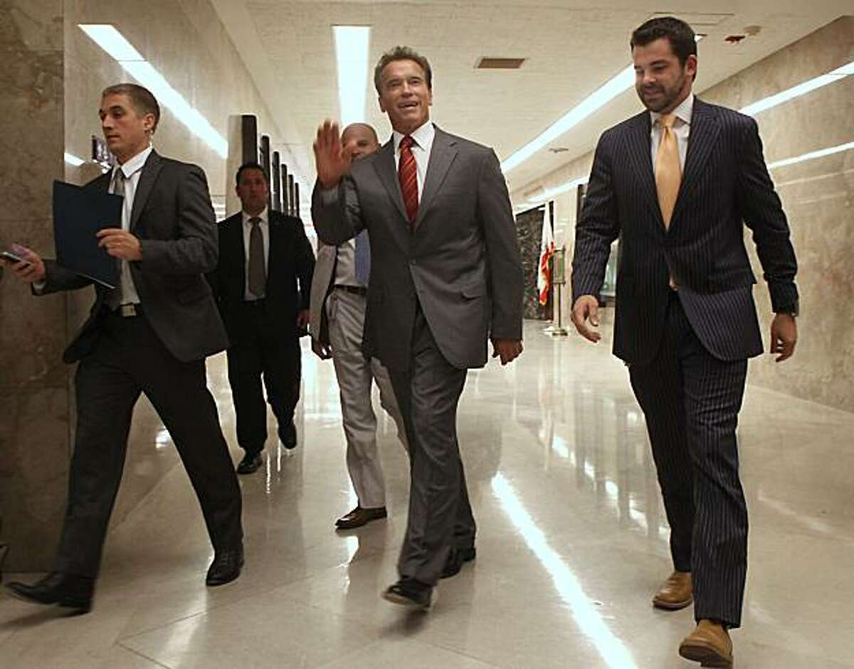 Gov. Arnold Schwarzenegger waves to well-wishers as he walks to a news conference at the Capitol in Sacramento, Calif., Wednesday, Sept. 1, 2010. Schwarzenegger refused to comment on GOP gubernatorial candidate Meg Whitman's comments blaming his lack ofleadership for the state's failure to pass a budget two months into the new fiscal year.
