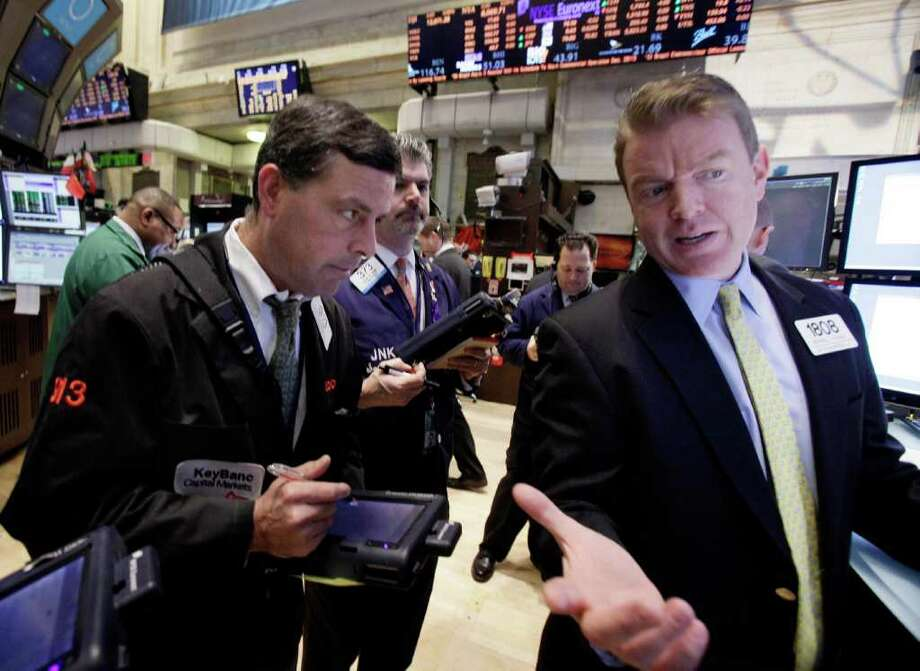 In this Feb. 8, 2012 photo, specialist Michael O'Mara, right, works on the floor of the New York Stock Exchange. Stock markets fell Friday, Feb. 10, 2012, after Greece's crucial international bailout was put on hold by its partners in the 17-nation eurozone, a day after it seemed that the country's tortuous journey to pacifying its creditors had reached a conclusion. (AP Photo/Richard Drew) Photo: Richard Drew